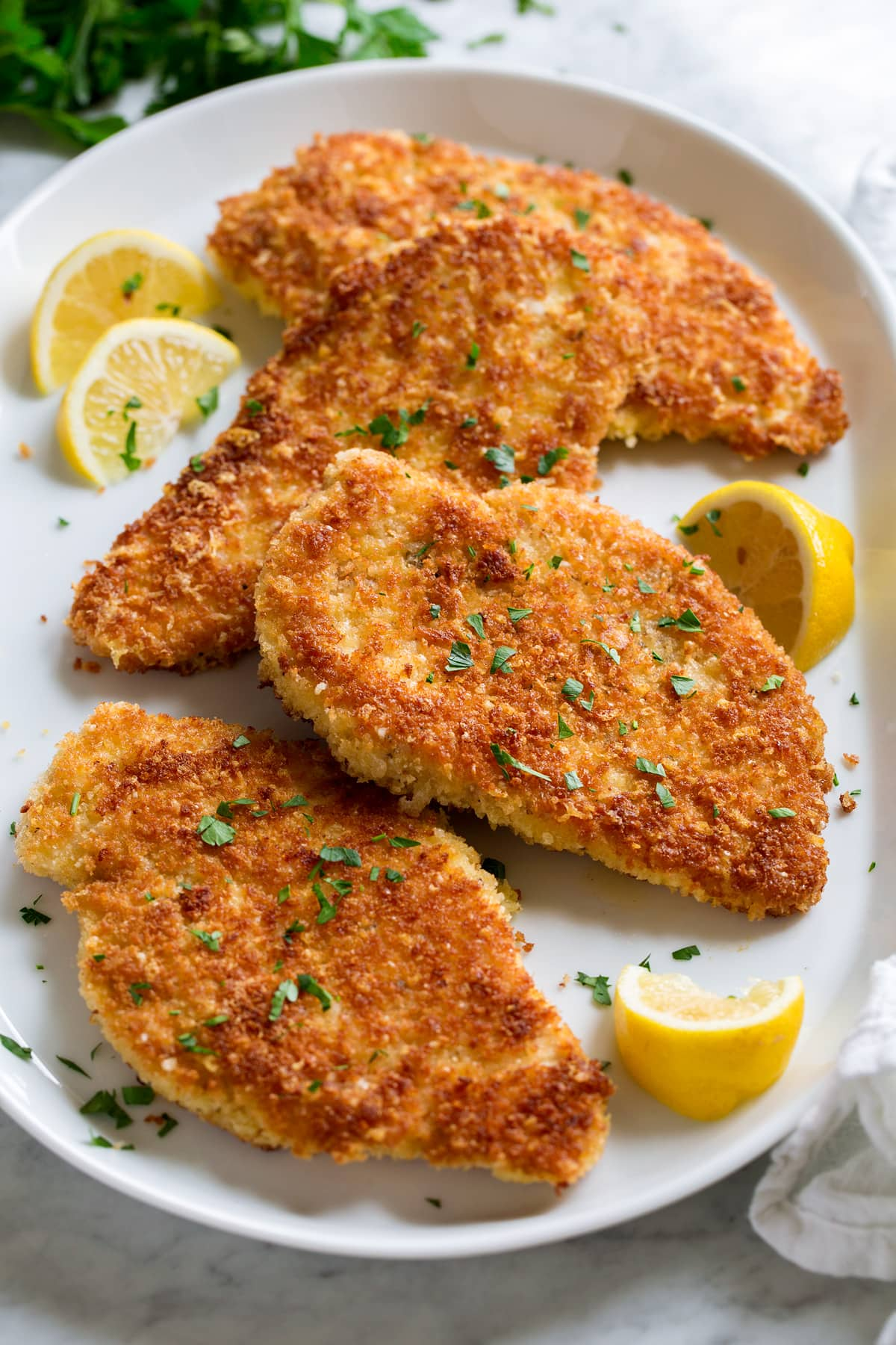 Parmesan Crusted Chicken cutlets shown on a white serving platter from a side angle. Lemons are shown to the side and parsley is garnished over.