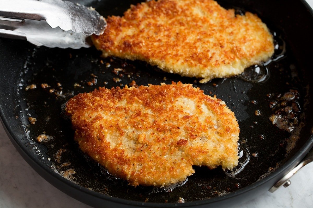 Parmesan chicken shown being fried in a skillet.