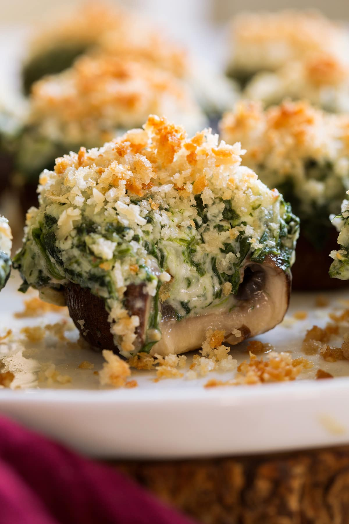 Stuffed mushrooms with a bite taken out to show cheesy filling.