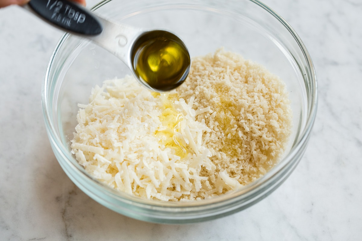 Preparing the panko mixture for stuffed mushrooms in a glass mixing bowl and drizzling with olive oil.