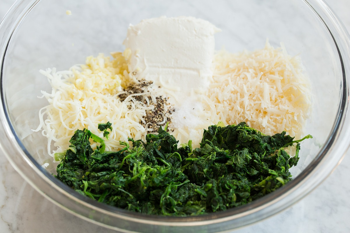 Second step of making stuffed mushrooms shown here, mixing the cheeses and spinach in a mixing bowl.