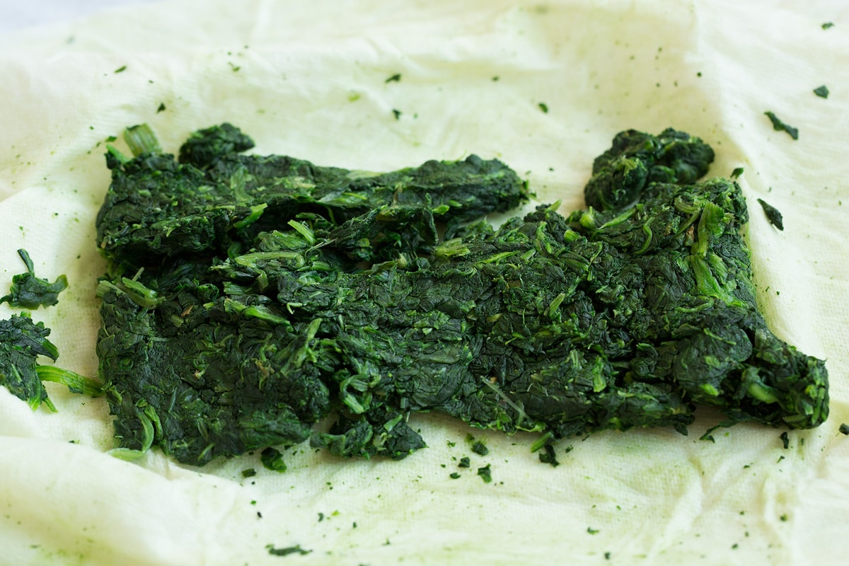 Spinach on paper towels shown after squeezing out the excess moisture. The first step to make stuffed mushrooms.