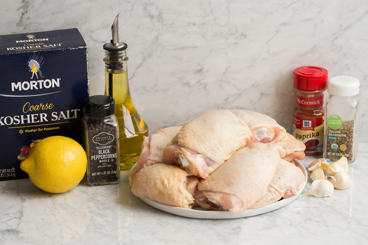 Image of ingredients needed to make baked chicken thighs. Shows raw chicken thighs, salt and pepper, olive oil, lemon, paprika, Italian seasoning and garlic.