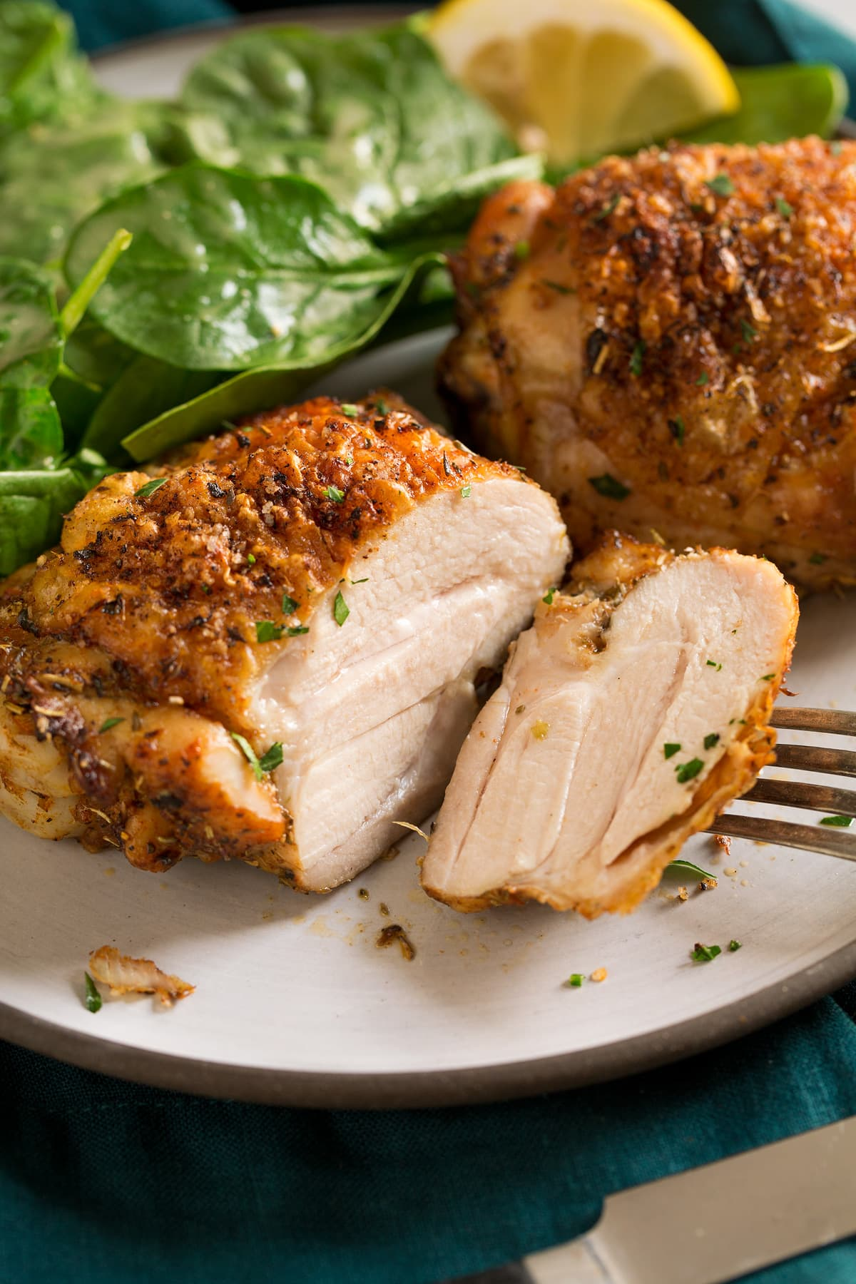 Baked chicken thigh sliced into on a serving plate.