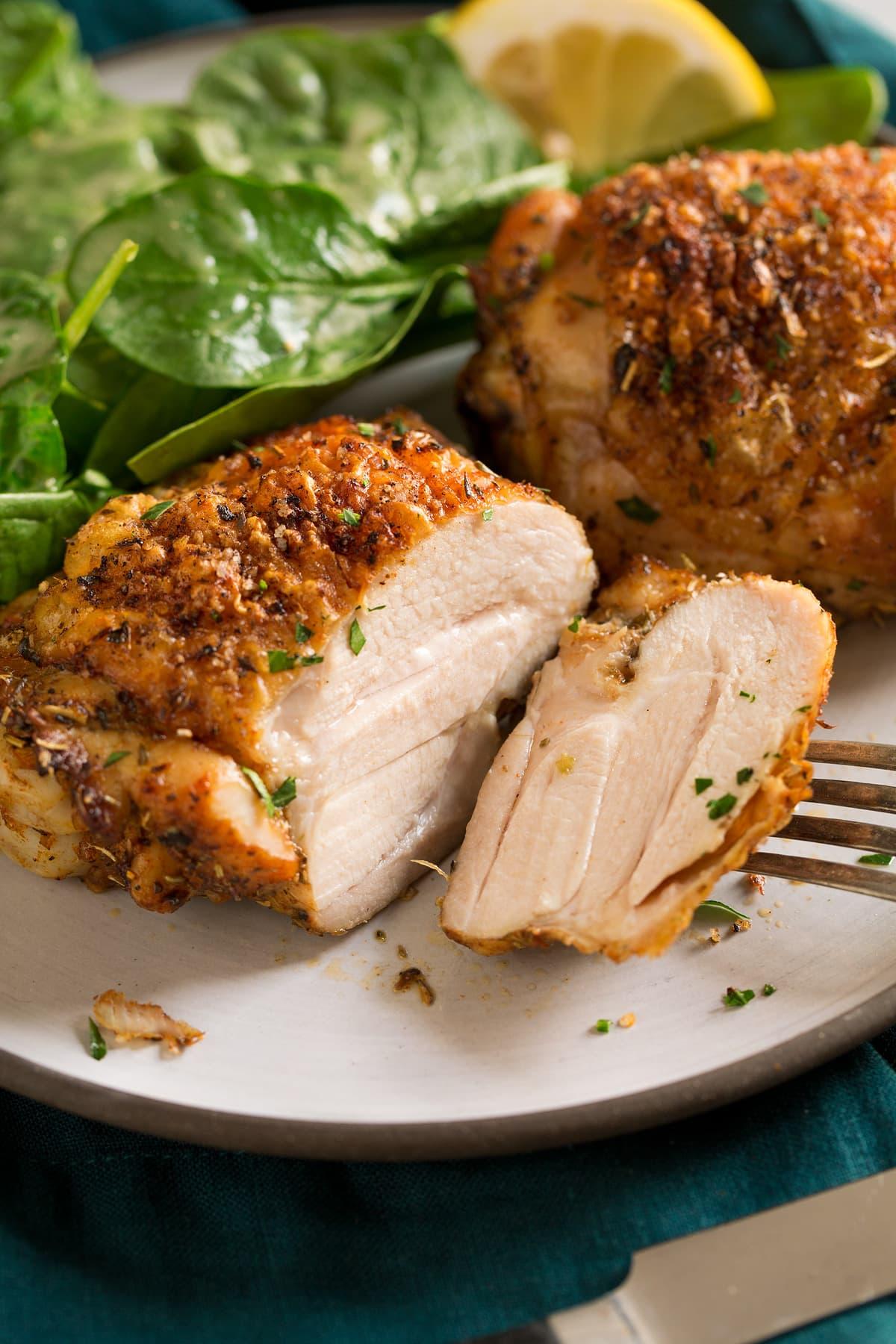 Muslo de pollo al horno cortado en rodajas en un plato para servir.