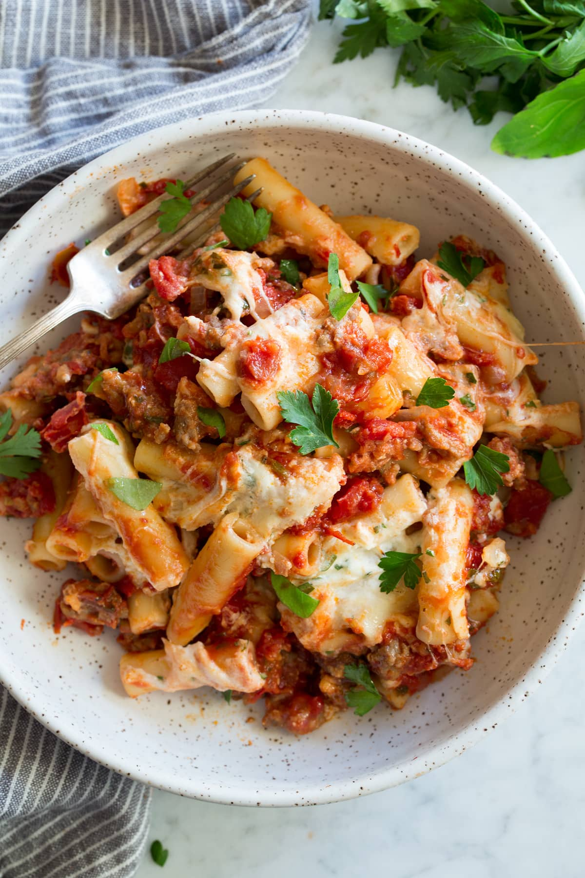 Bowl of baked ziti including ziti pasta, sausage, marinara sauce, three types of Italian cheese and fresh herbs.