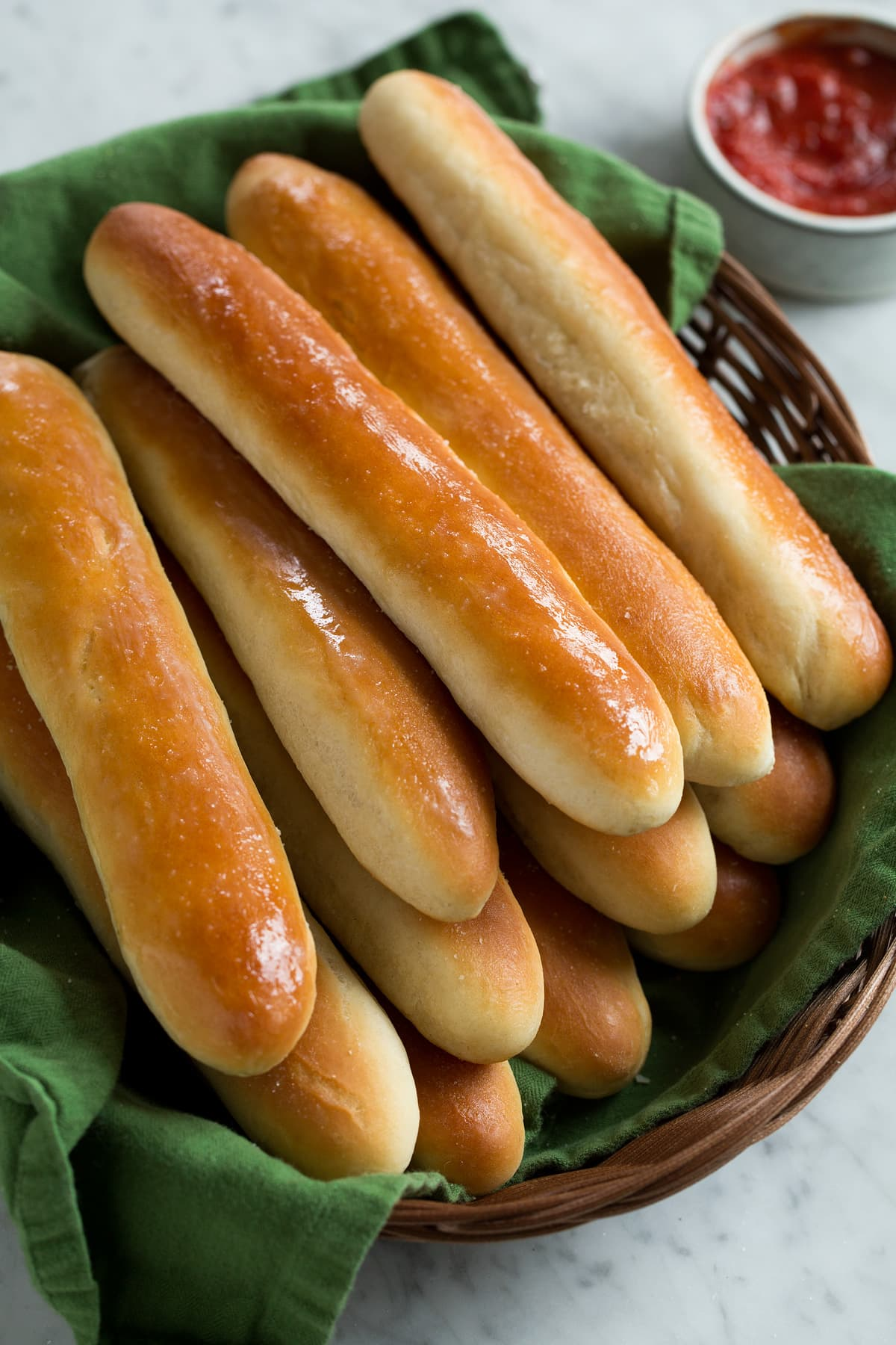 Breadsticks stacked in a wicker basket lined with a green kitchen cloth.