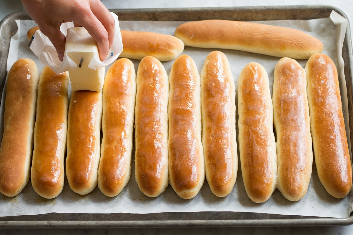 Buttering breadsticks on a baking sheet with a stick of butter.