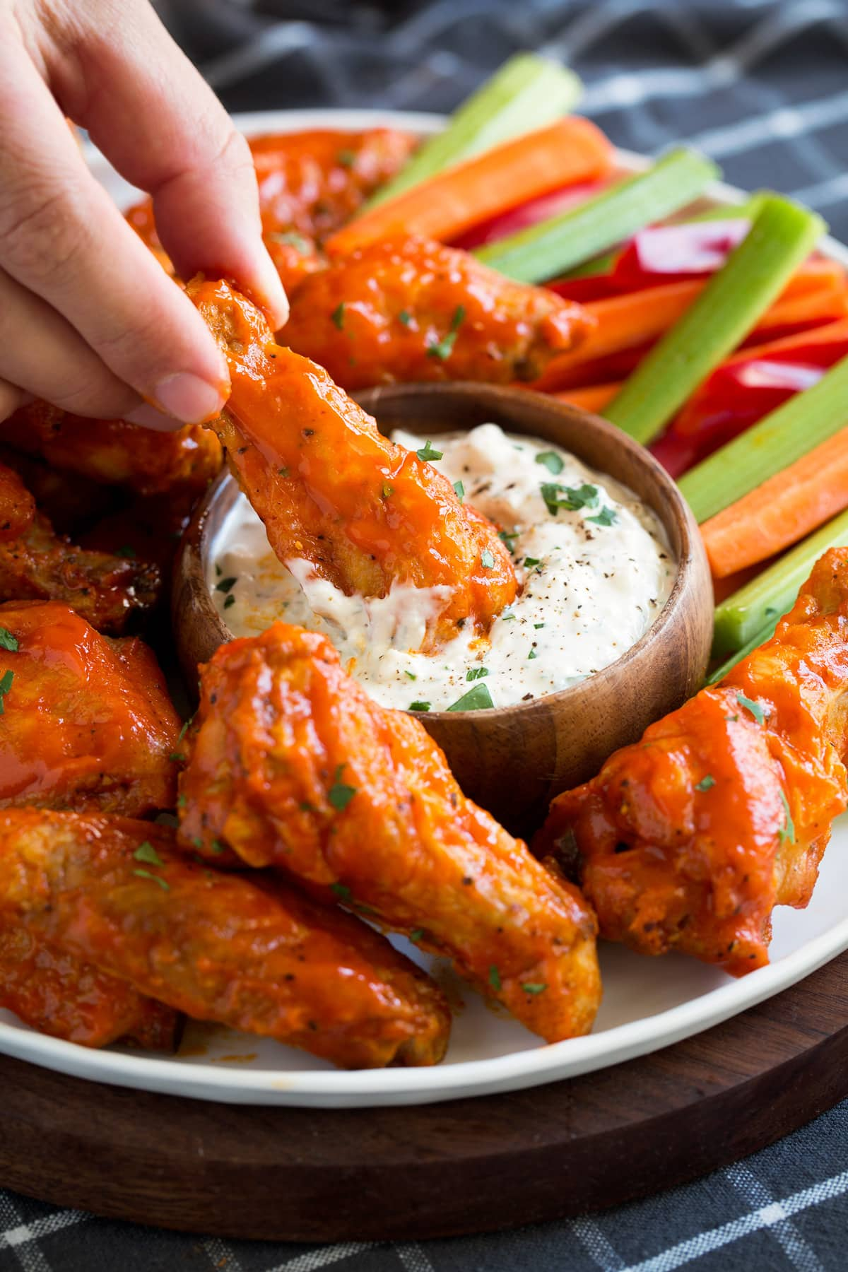Buffalo wings dipped in blue cheese dip.