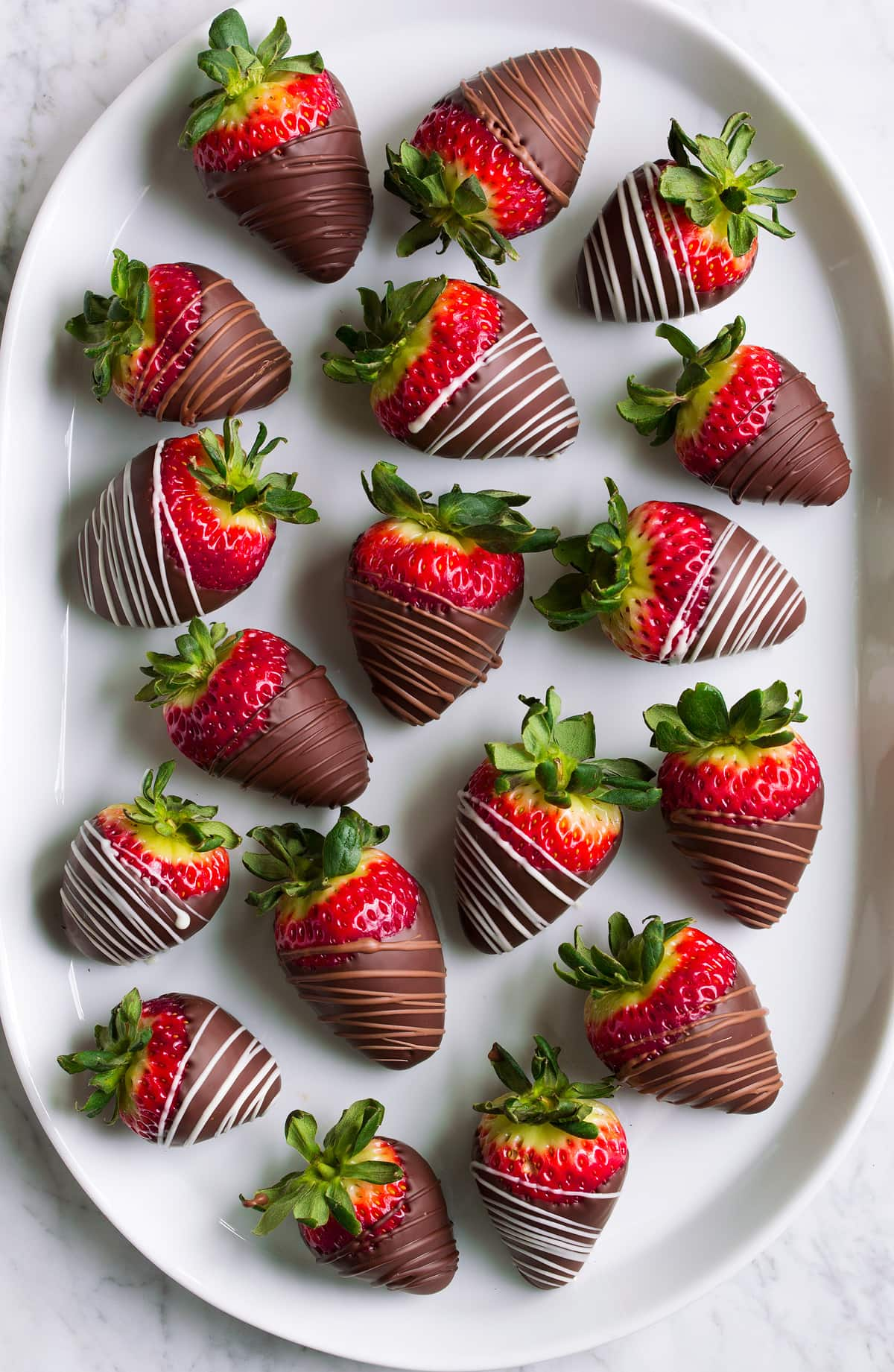 Chocolate dipped strawberries on an oval white platter.