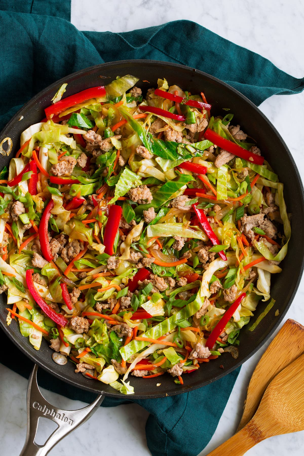 Overhead image of egg roll in a bowl in a skillet shown after completed cooking. In it you see cabbage, ground turkey, red bell pepper, and carrots.