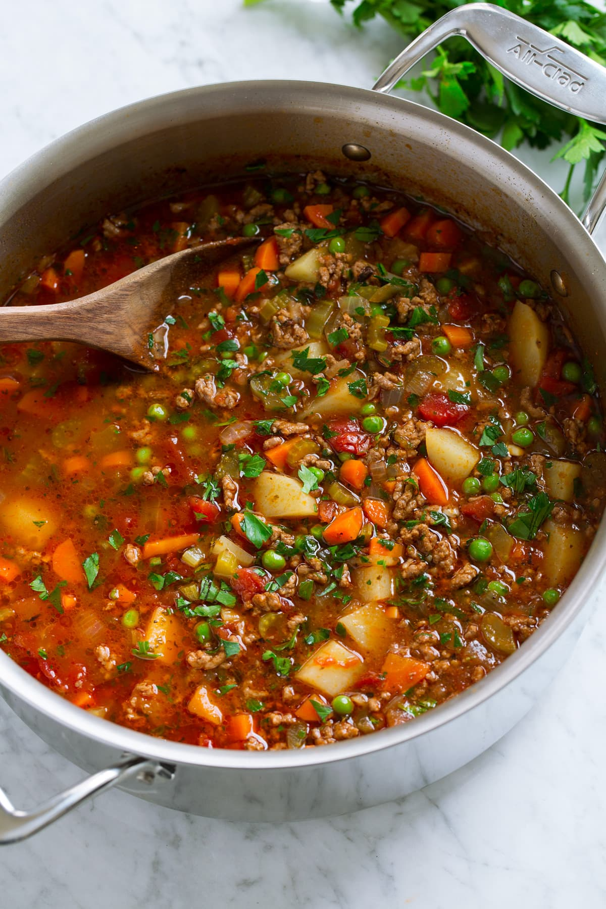 Stainless steel pot full of ground beef hamburger soup with potatoes, carrots, peas, celery, tomatoes, herbs and broth.