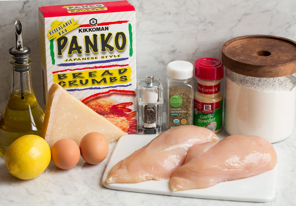 Photo of ingredients in parmesan crusted chicken. Includes chicken breasts, panko bread crumbs, flour, eggs, garlic powder, Italian seasoning, lemon, parmesan, olive oil, salt and pepper.