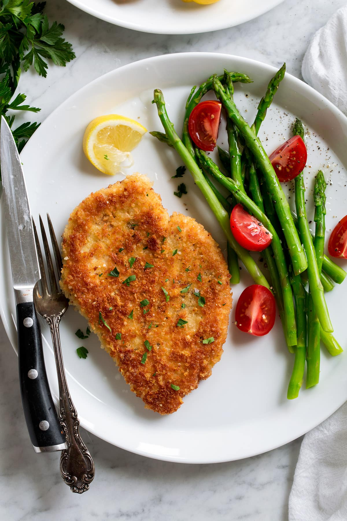 Parmesan Crusted Chicken fried breast shown on a serving plate with a side of asparagus and tomatoes.