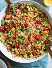 Quinoa Salad in a large serving bowl with wooden tongs on the side.