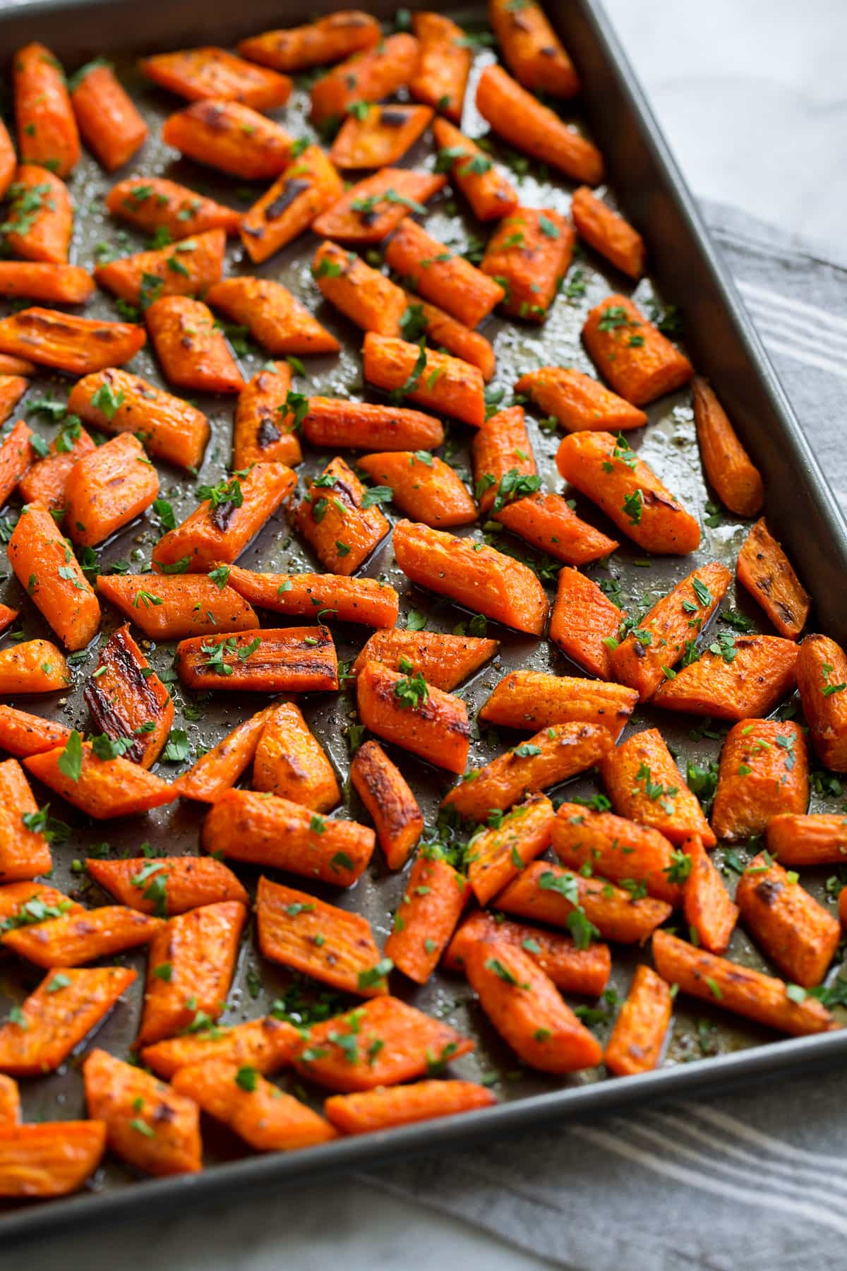 Photo: Roasted carrots shown from the side on a dark baking sheet.