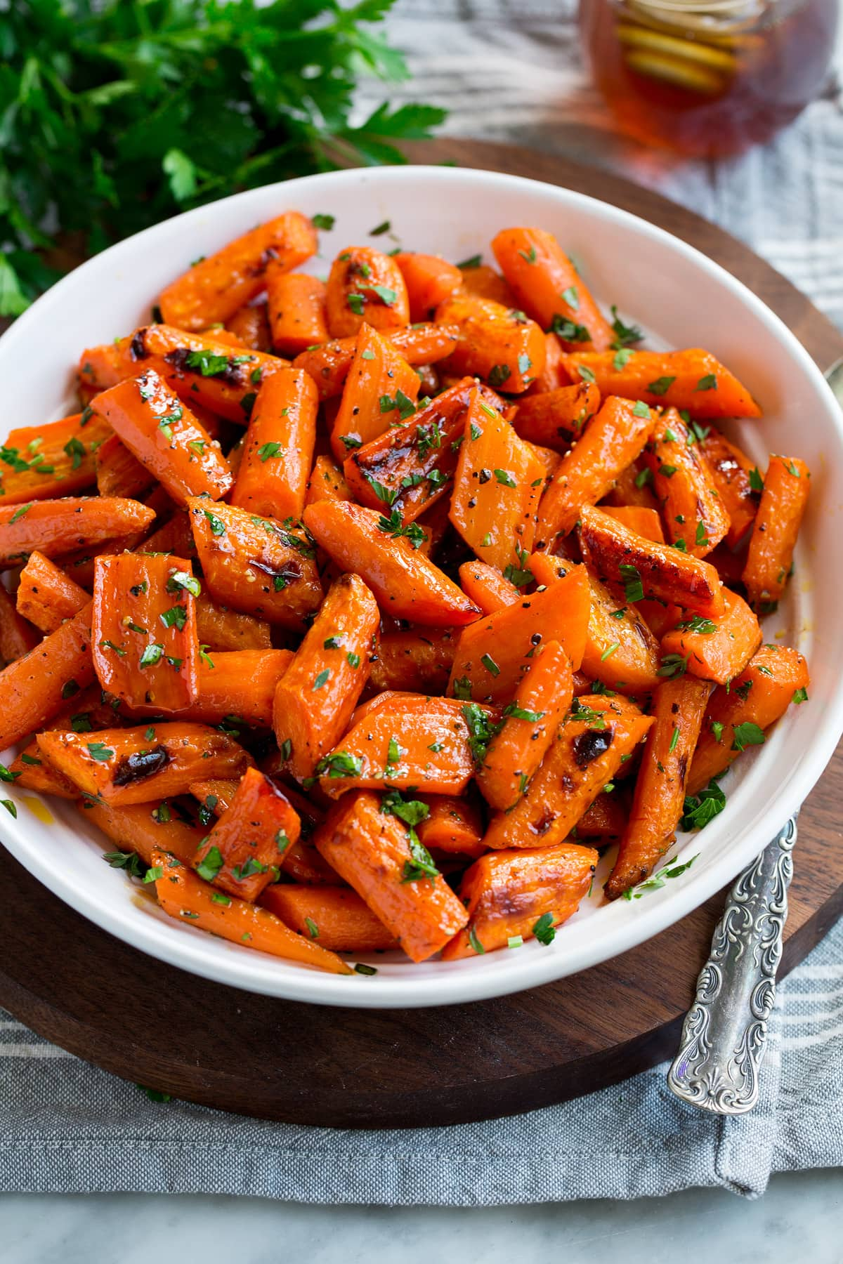 Photo: Roasted carrots in a white serving bowl. Carrots are garnished with parsley with a bunch in the background. Bowl is resting on a wooden platter and a grey cloth.