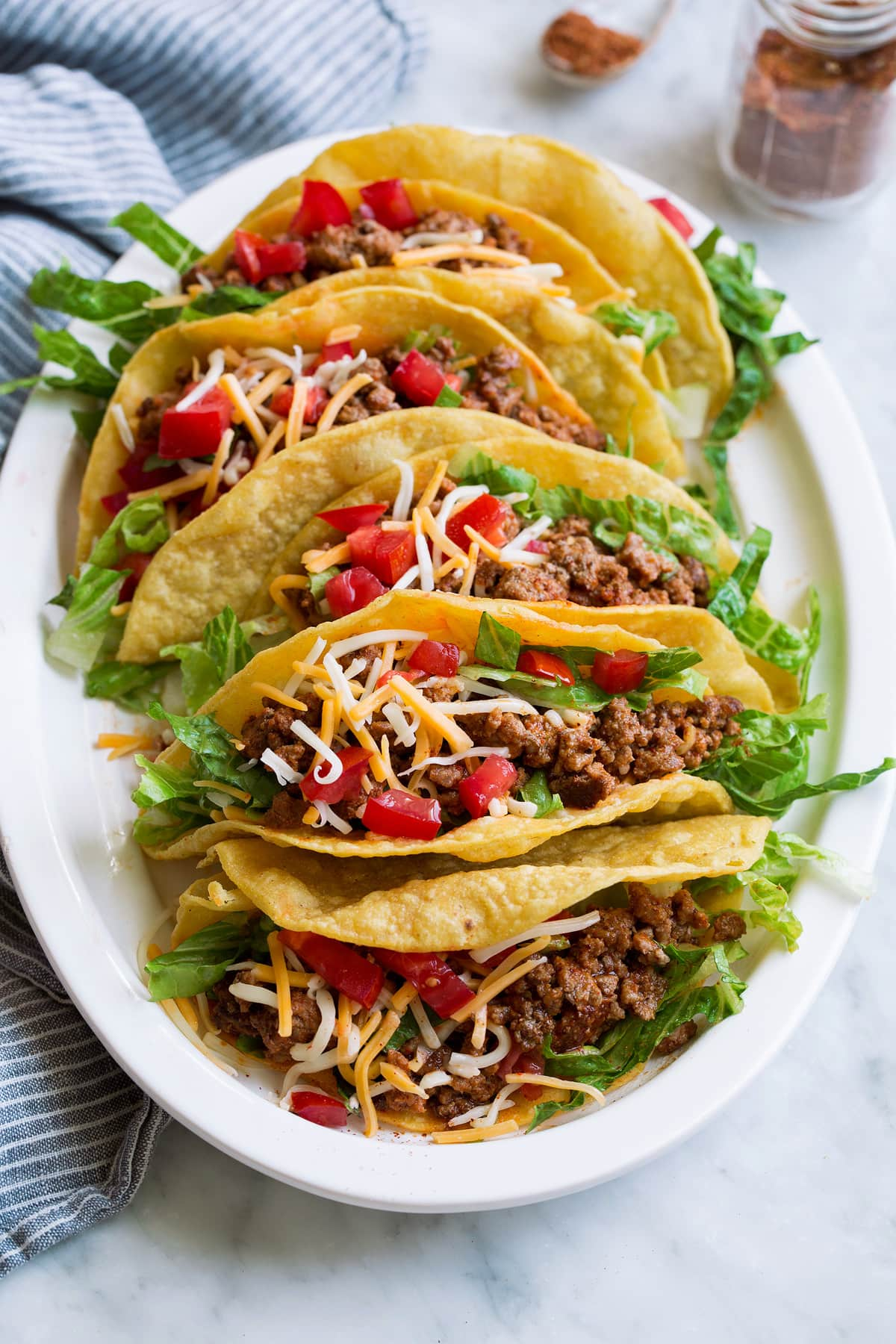 Photo of ground beef tacos on a platter which have been seasoned with a homemade taco seasoning. Showing how to use the DIY taco seasoning.