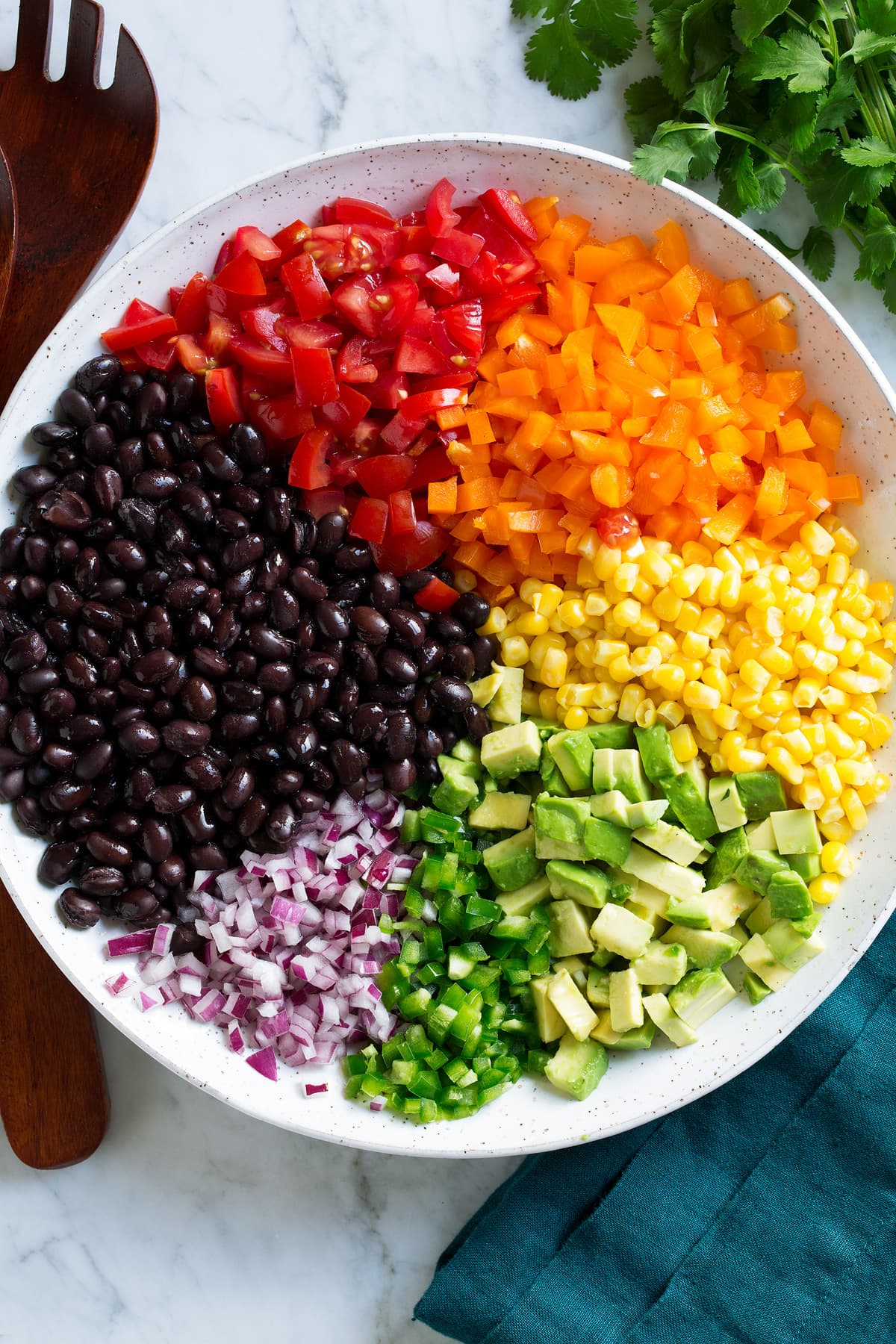 Black bean and corn salad ingredients in a mixing bowl before tossing together.