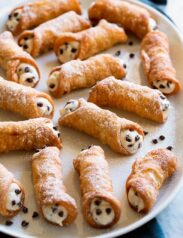 Cannoli with ricotta and chocolate chip filling on a white serving platter.