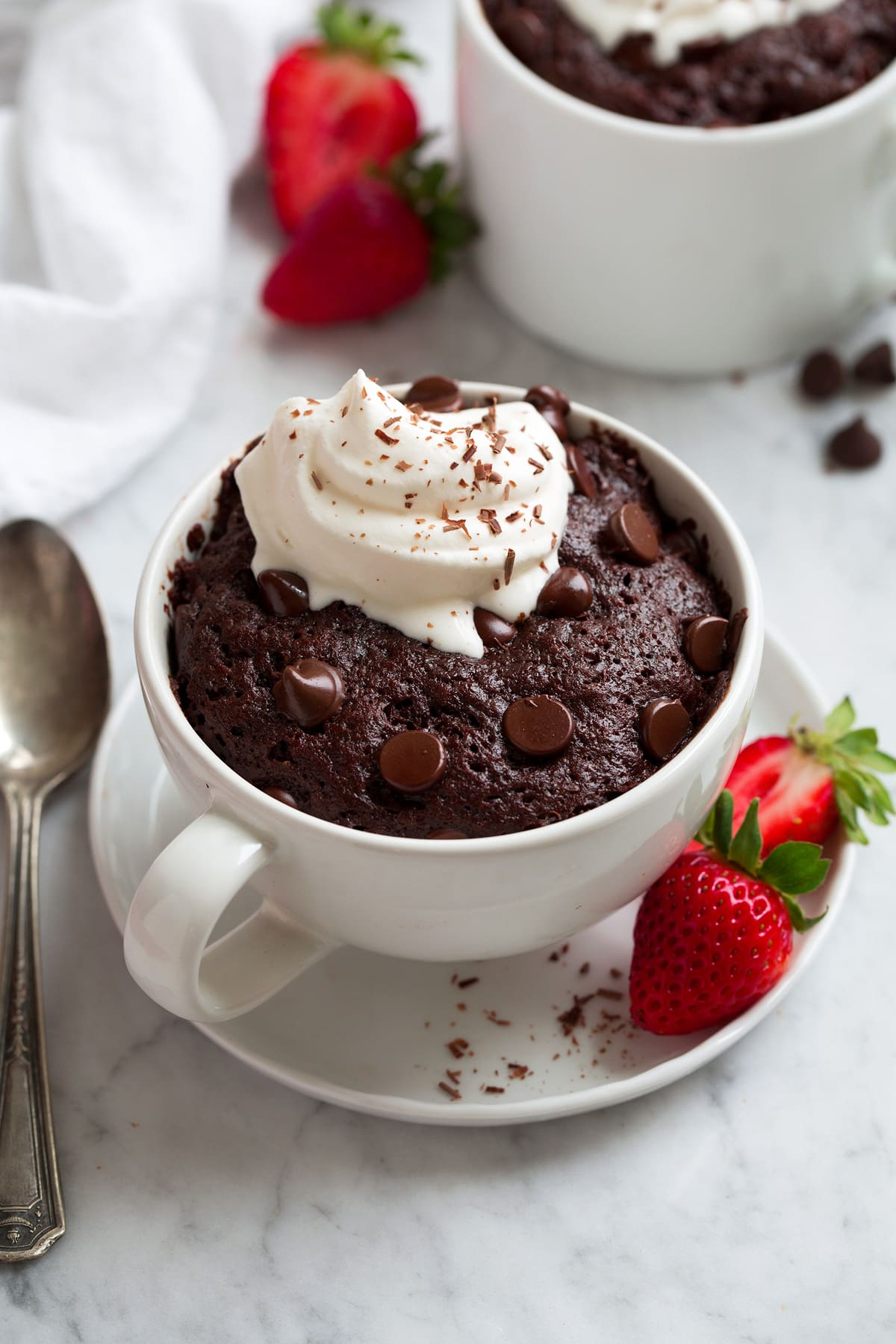 Chocolate Mug Cake with chocolate chips and dollop of whipped cream on top.