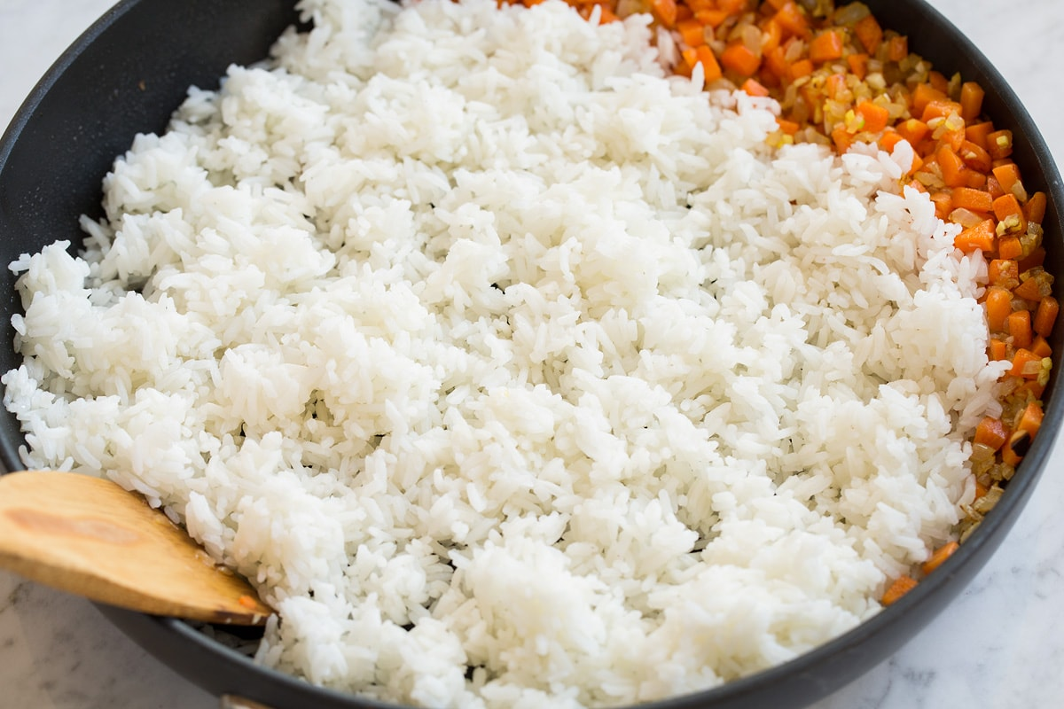 Frying white rice in a skillet with vegetables.