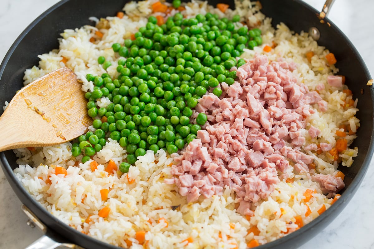 Peas and ham added to fried rice mixture in skillet.