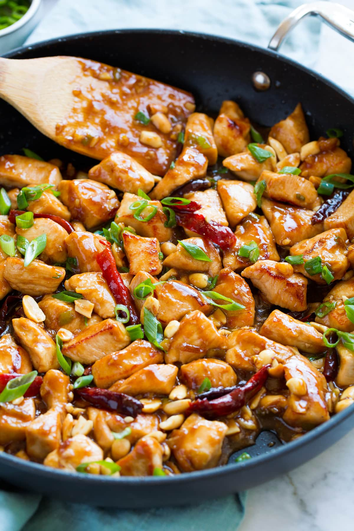 Close up image of Kung Pao chicken in a large skillet shown from a side angle.