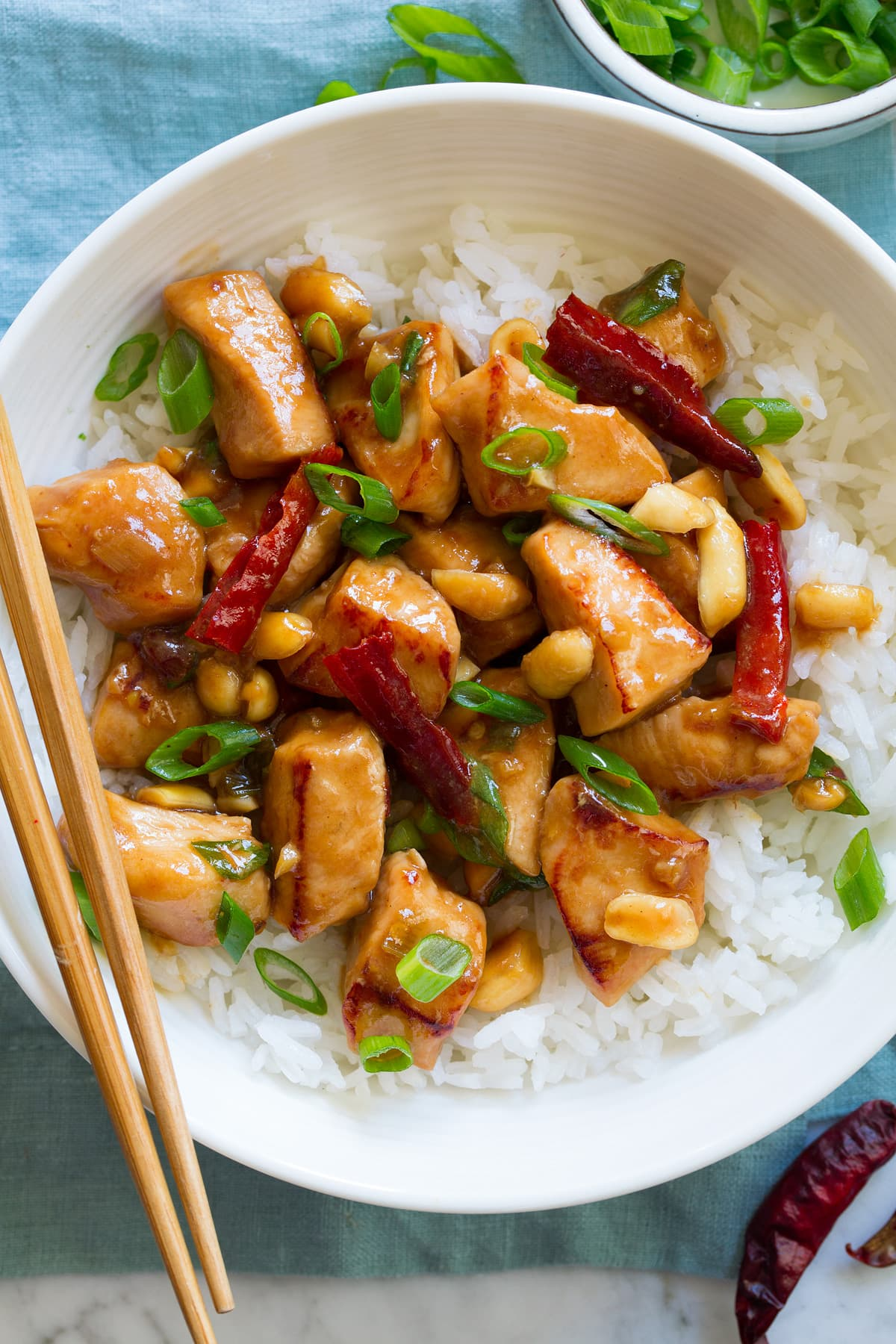 Overhead image of white bowl filled with rice topped with kung pao chicken. Chop sticks are shown to the side.