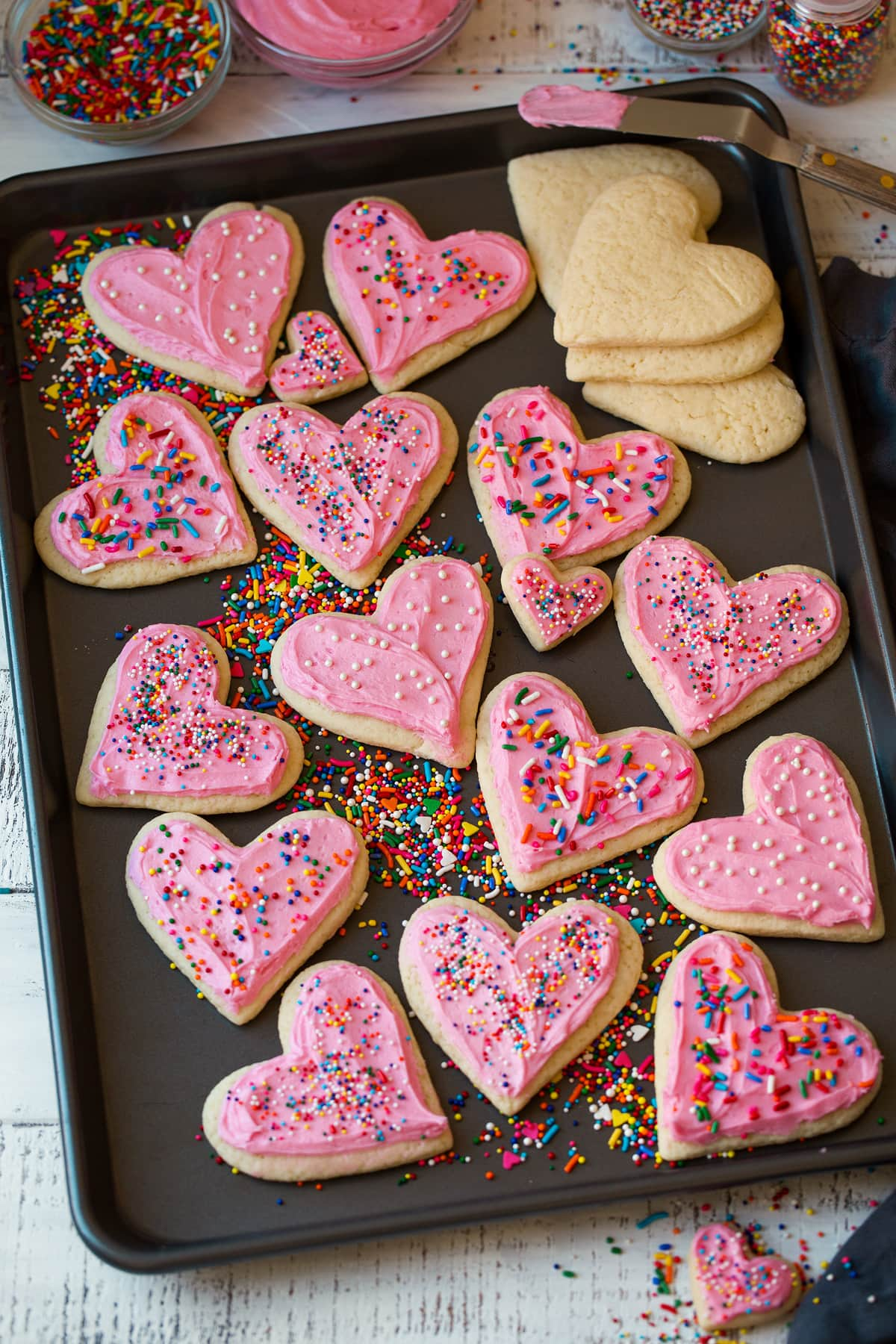 Cutout sugar cookies in heart shapes on a baking sheet shown frosted with sprinkles.
