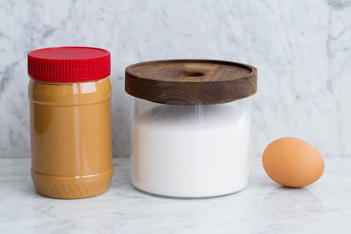Image of ingredients including creamy peanut butter, granulated sugar in a glass jar and 1 egg.