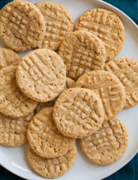 3 Ingredient Peanut Butter Cookies laying stacked on top of each other on a white serving plate.