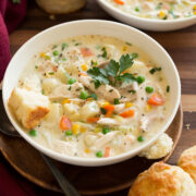 Two bowls of chicken pot pie soup in white serving dishes set over wooden a wooden tabletop. Biscuits are served to the side.