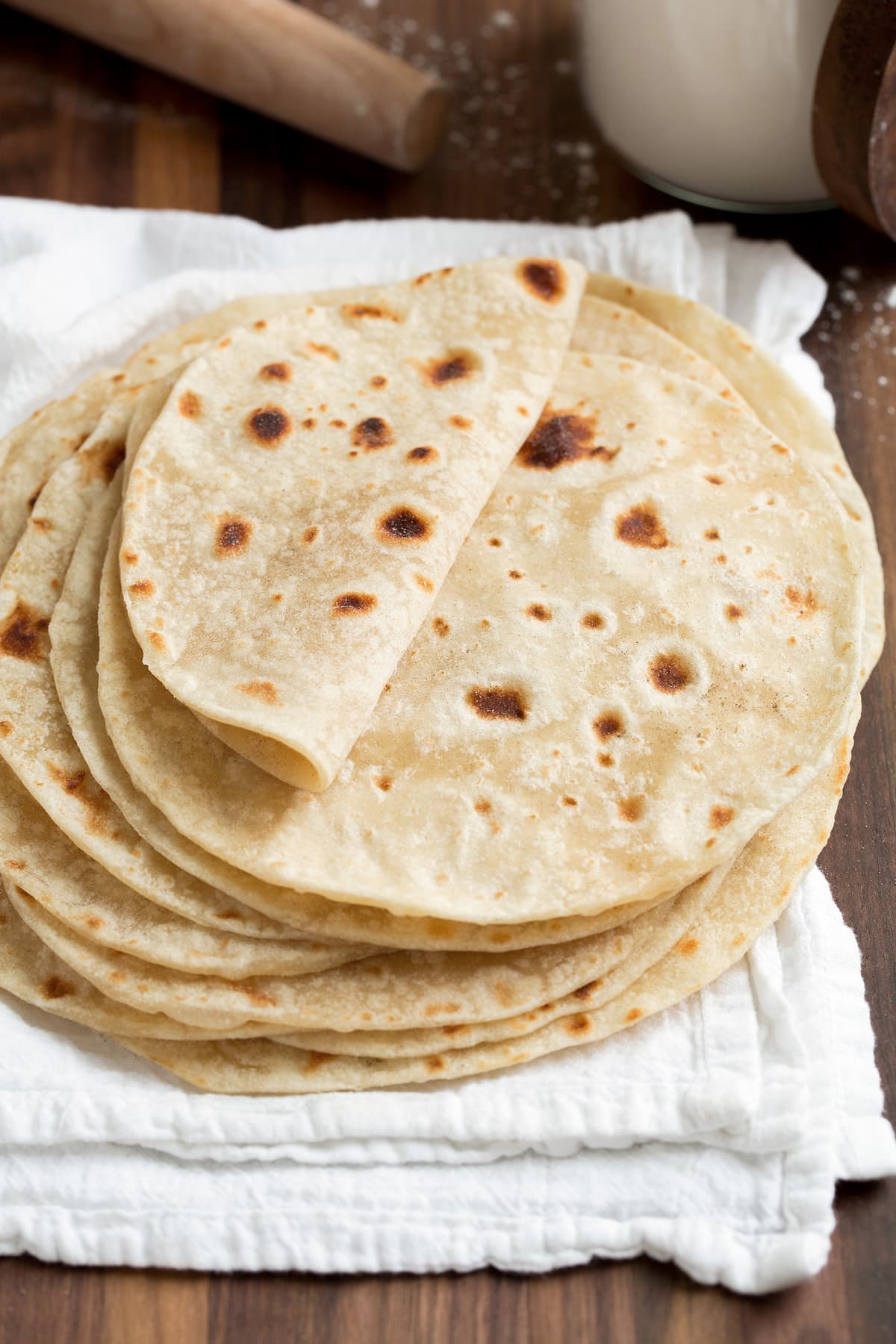 Stack of homemade flour tortillas on a white kitchen cloth. Top tortilla is folded over to show soft and moist texture.