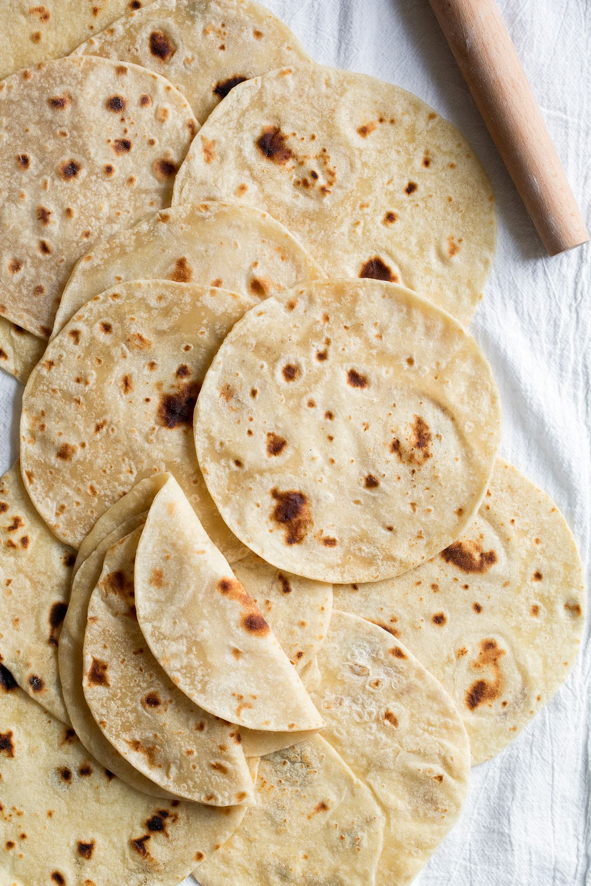 Overhead image of flour tortillas layered across each other on a white kitchen cloth.