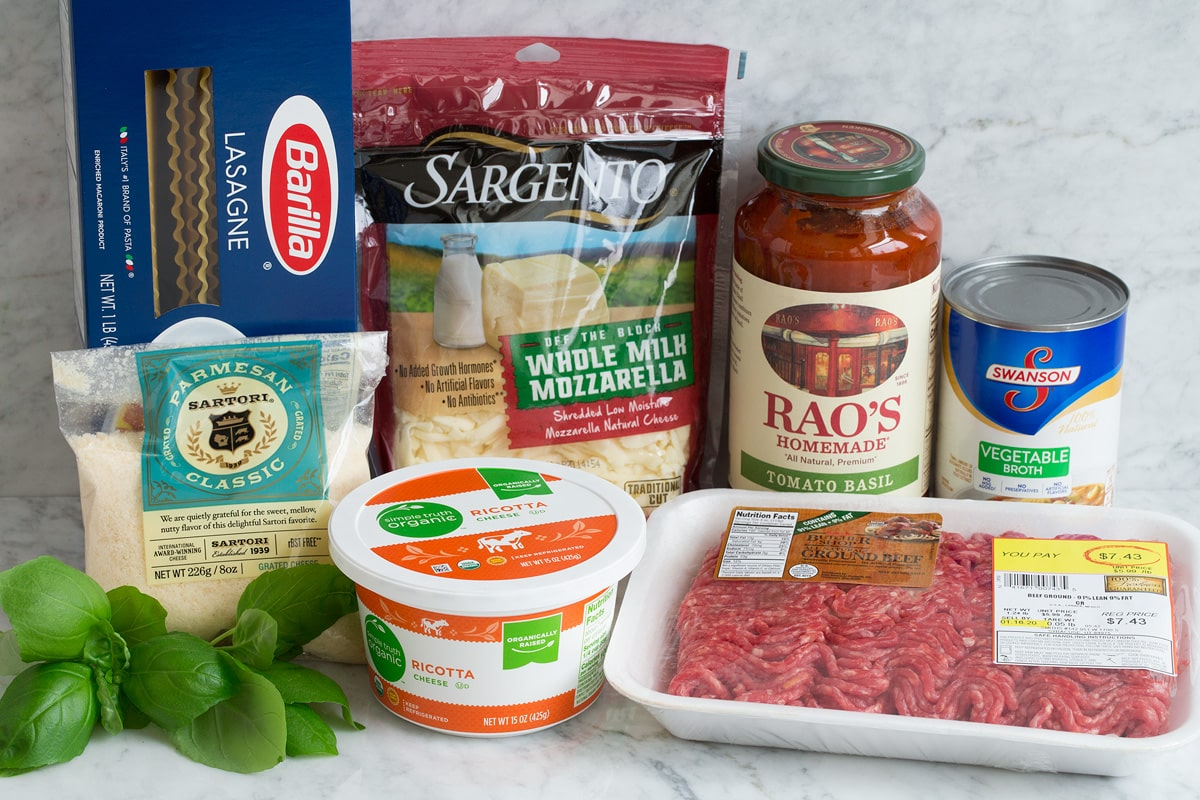 Image showing ingredients used to make an easy lasagna. Includes lasagna noodles, parmesan, basil, ricotta, mozzarella, bottled marinara, ground beef and vegetable broth.