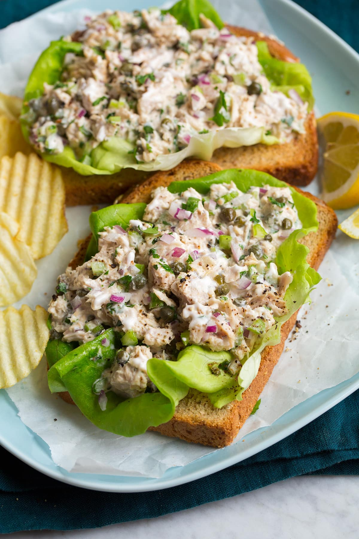 Tuna salad shown on bread slices over lettuce leaves.
