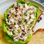 Tuna salad atop bread slices and lettuce leaves. Shown on a white plate with a side of potato chips.