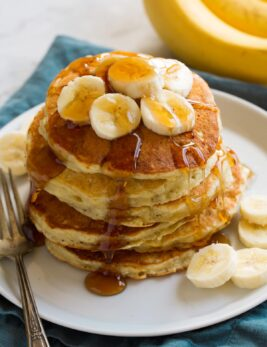 Stack of banana pancakes on a plate. Pancakes are topped with banana slices and maple syrup.