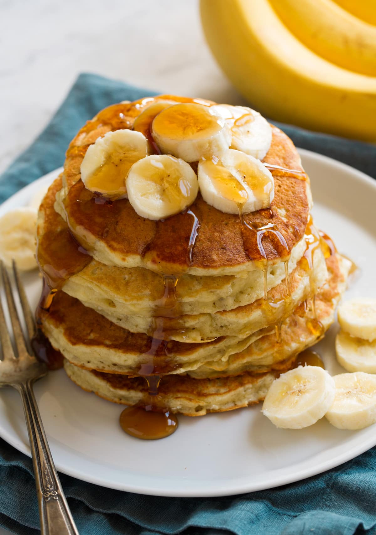 Stack of homemade banana pancakes on a plate. Pancakes are topped with banana slices and maple syrup.