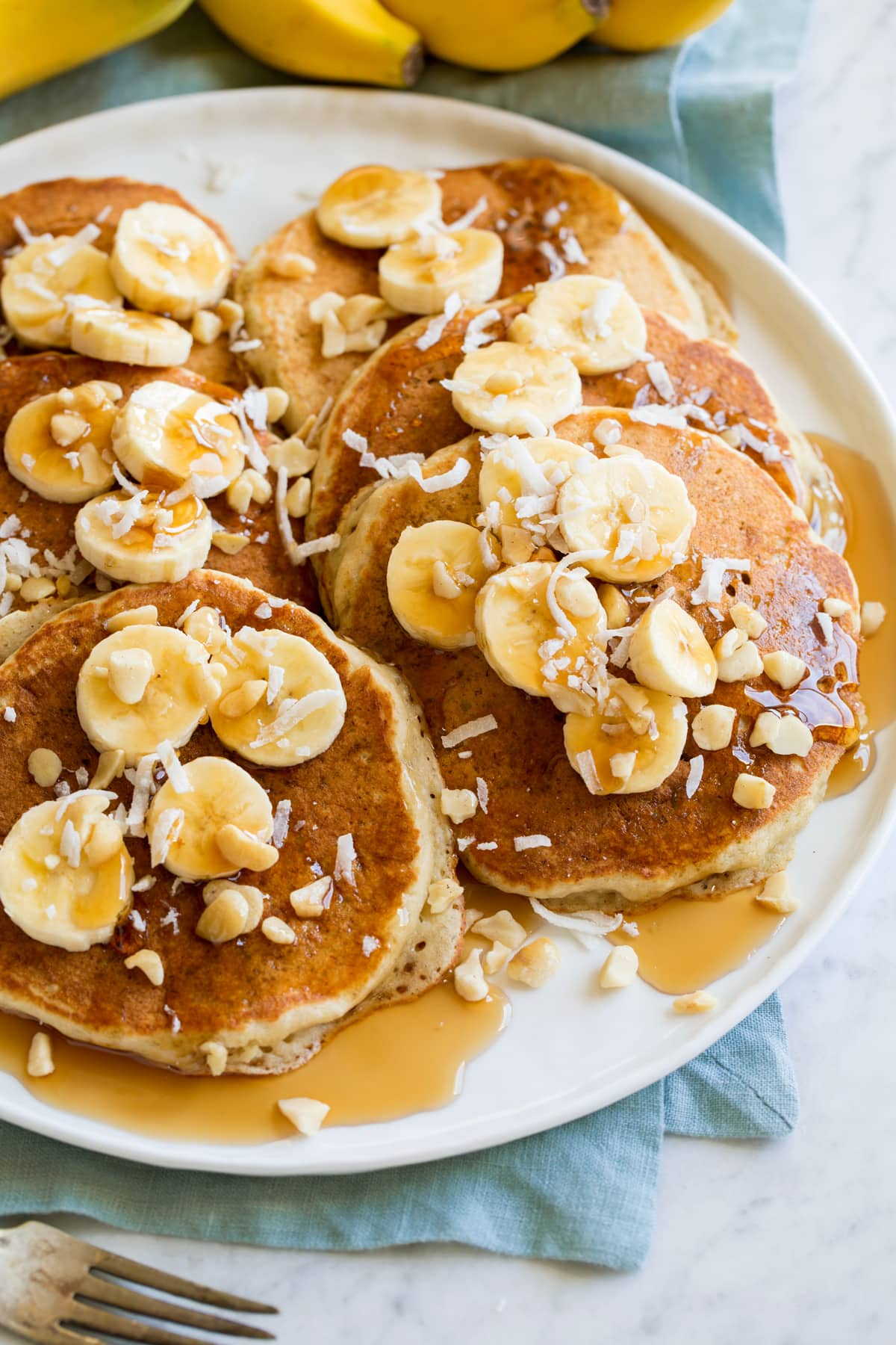 Banana pancakes topped with nuts, banana slices, coconut and maple syrup on a serving plate.
