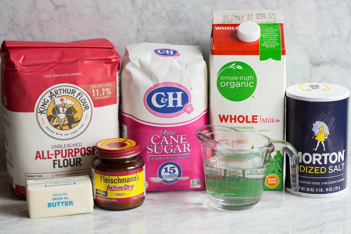 Image of ingredients used to make white bread. Includes all-purpose flour, sugar, milk, salt, water, yeast and butter.