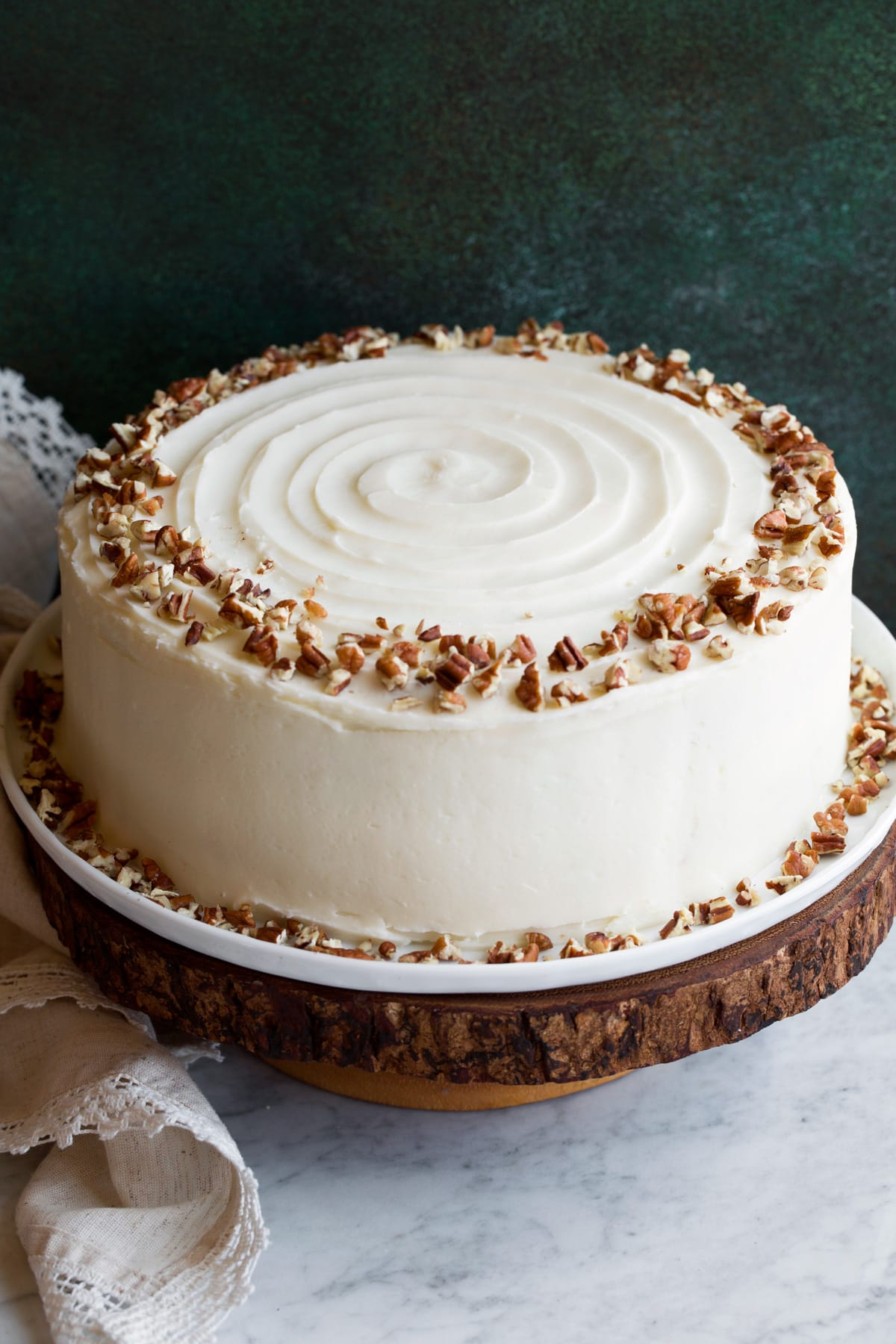 Cake on a wooden cake stand covered in cream cheese frosting and garnished with a wring of chopped pecans on top.