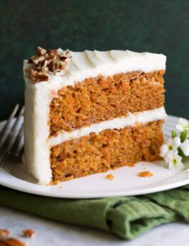 Slice of carrot cake with cream cheese frosting on a white dessert plate sitting on a green cloth napkin.
