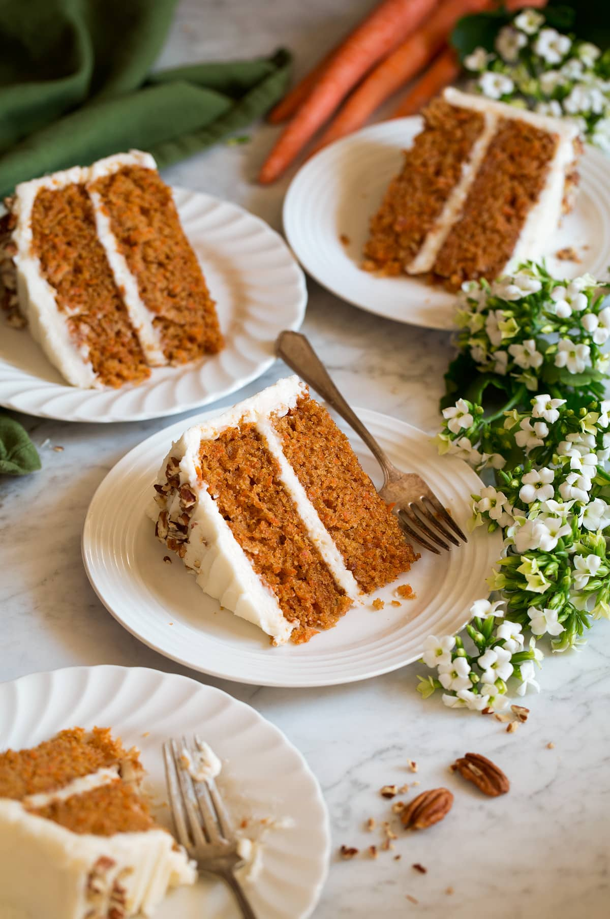 Four slices of carrot cake shown on white scalloped dessert plates with flowers and carrots around plates.