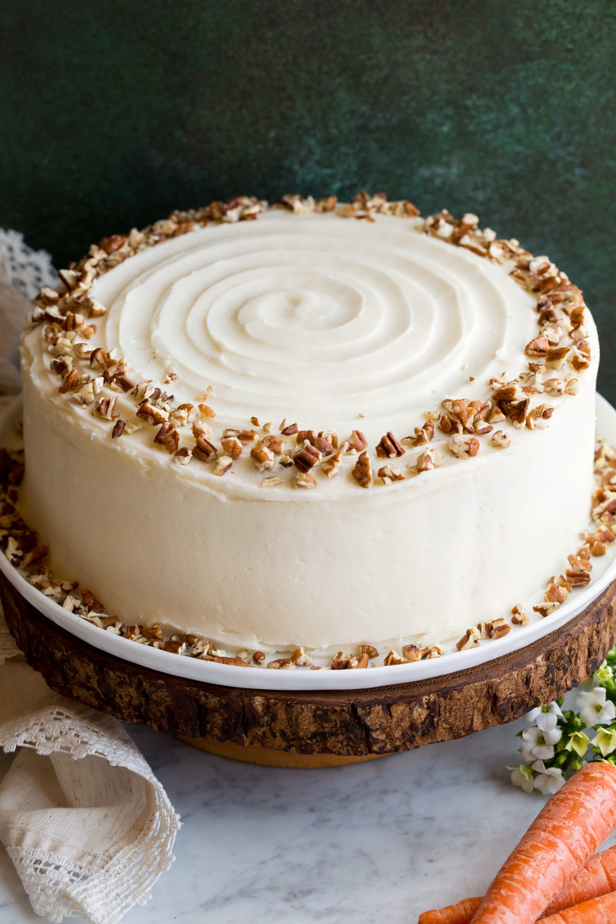 Whole carrot cake sitting on a wooden cake stand.