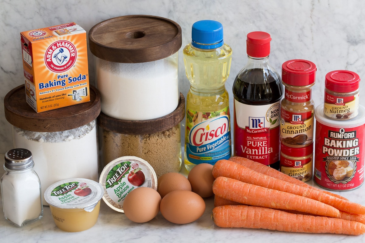 Ingredients that are used to make carrot cake shown here including salt, flour, white sugar, brown sugar, applesauce, baking soda, eggs, carrots, vegetable oil, vanilla, cinnamon, nutmeg, ginger and baking powder.
