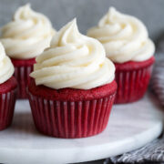 Cream cheese frosting shown piped over red velvet cupcakes.