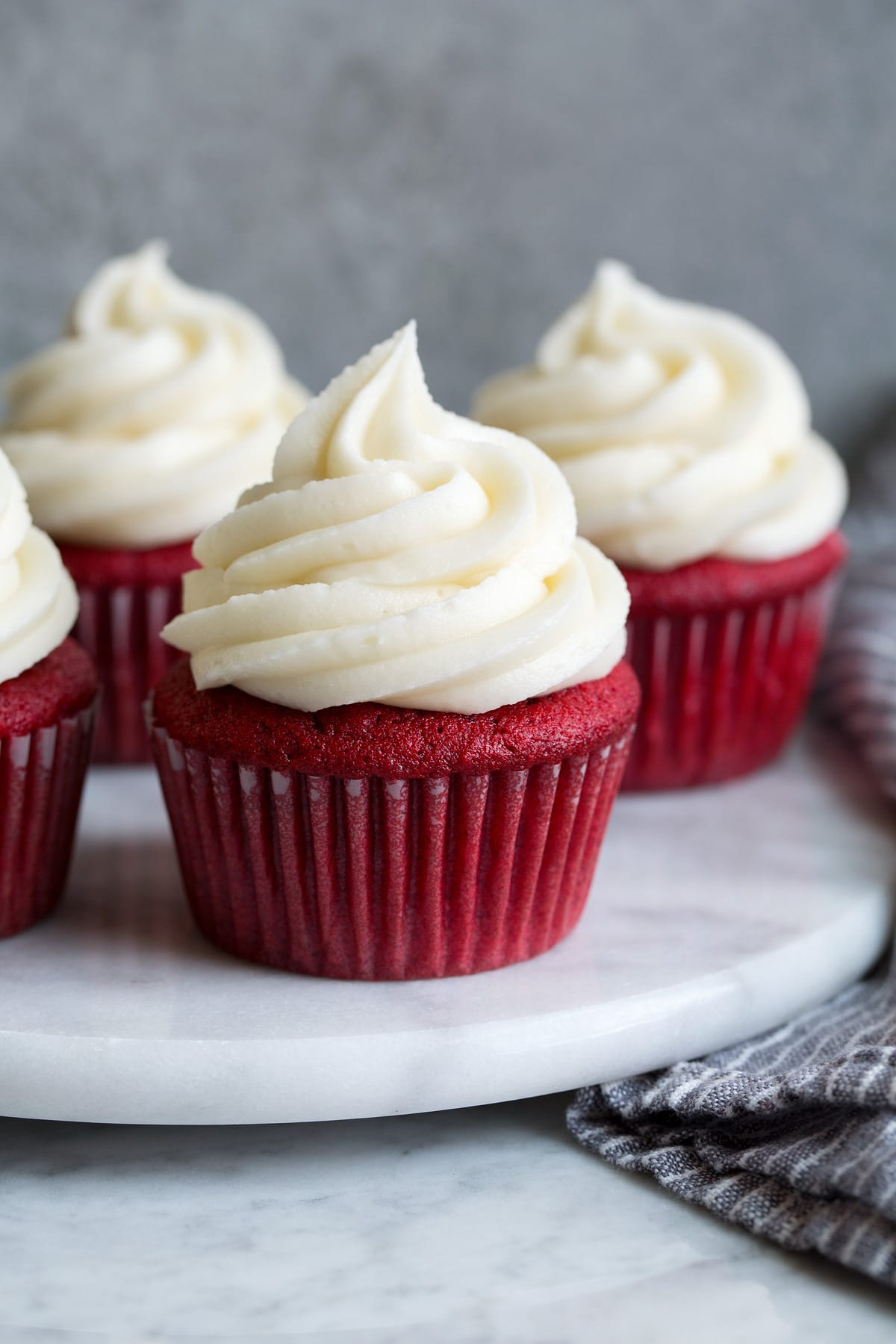 Cream cheese frosting shown atop four red velvet cupcakes on a marble platter.