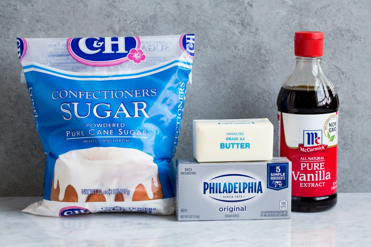 Ingredients used to make cream cheese frosting shown here including powdered sugar, cream cheese, butter and vanilla extract.